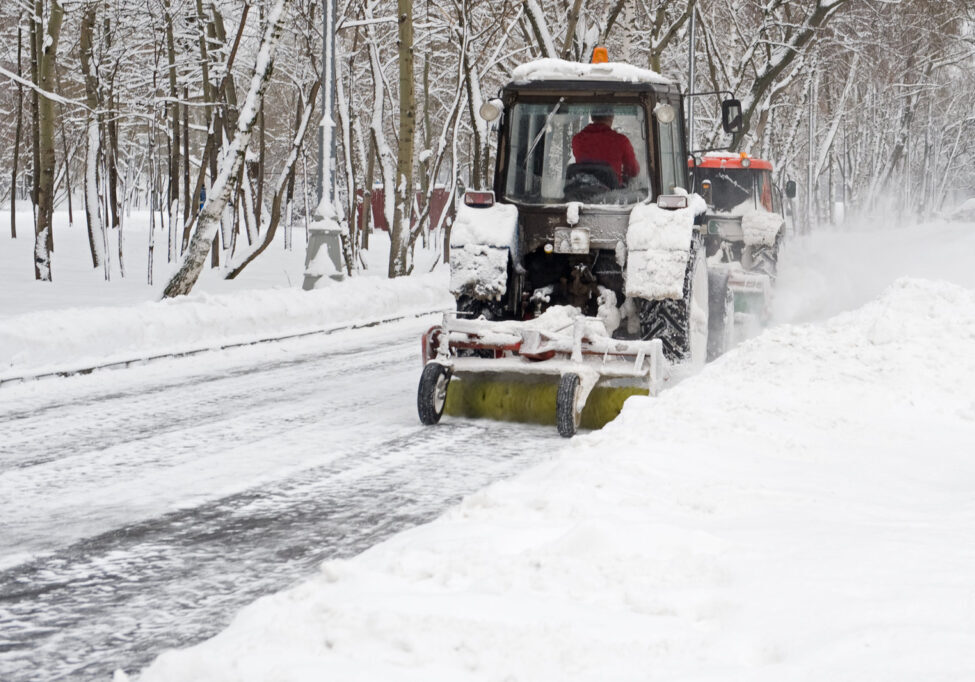 worker clearing up the snow road